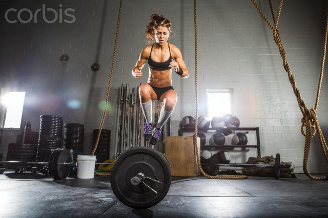 Female athlete jumping over barbell